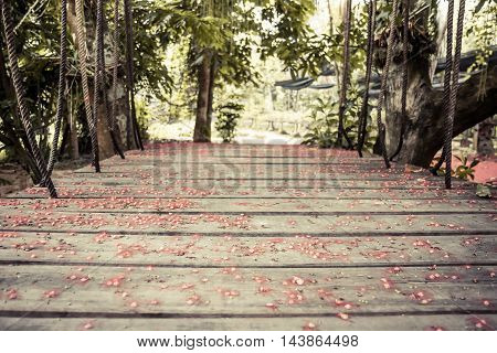 Old wooden suspension bridge with ropes in tropical forest covered with red flowers with selective focus on wooden planks and blurred background