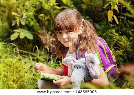 nice little cute girl reading a book with elephant