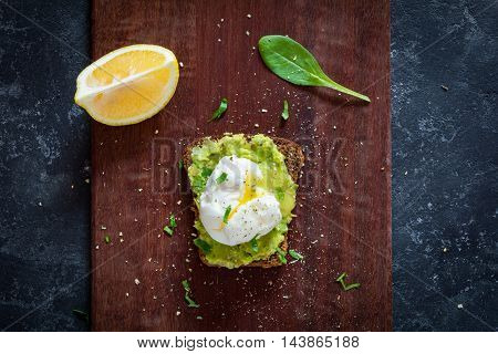 Avocado poached egg sandwich on wooden chopping board, top view