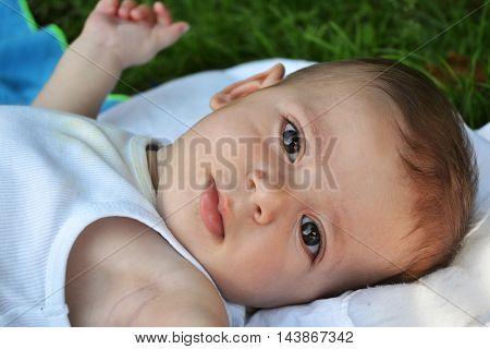 Beautiful and happy outdoor baby boy close up portrait.