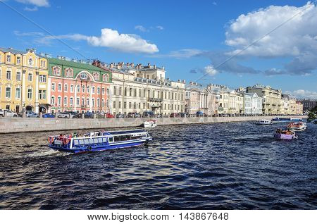 ST. PETERSBURG, RUSSIA - AUGUST 12, 2016: Pleasure boats with tourists on the Fontanka River near the Panteleimon bridge in St. Petersburg