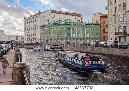 ST. PETERSBURG, RUSSIA - AUGUST 14, 2016: Pleasure boat with tourists on the Moika River near the Griboyedov Canal