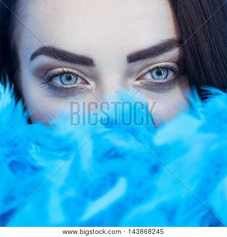 Closeup portrait of beautiful seductive brunette woman smiling and looking into the camera while playing with blue feather boa over blue wall background