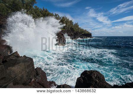 A big wave breaks on a rocky shoreline