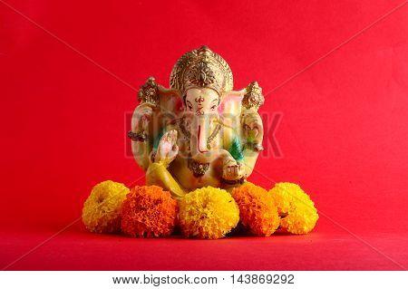 Hindu God Ganesha. Ganesha Idol on red Background.