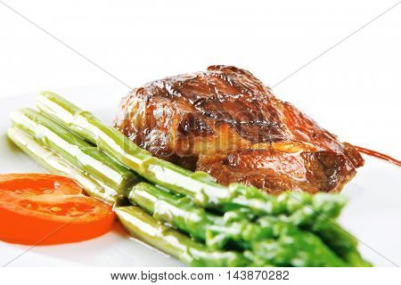 beef meat served with asparagus on white dish .  shallo