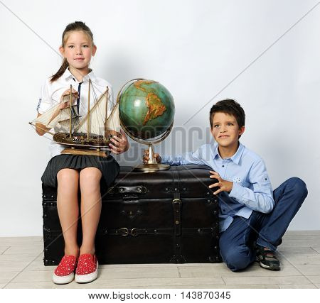 children with old globe and ship
