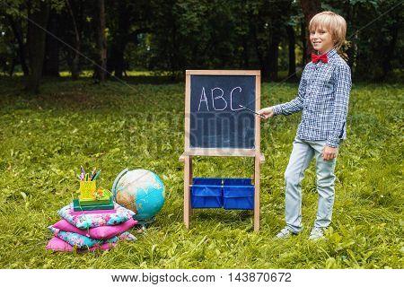 smart little boy writes letters on a school board