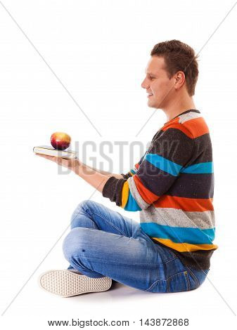 Sound mind in healthy body - concept of mental nutrition - man with book and apple white background
