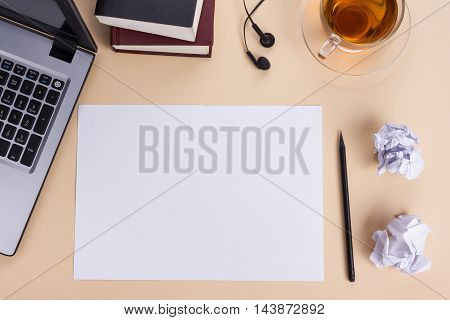 Office table desk with set of colorful supplies, white blank note pad, cup, pen, pc, crumpled paper, flower on beige background. Top view and copy space for text.