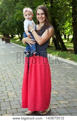 Mother with a baby standing on the road in the park
