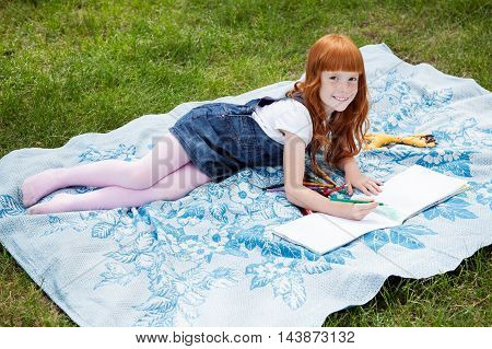 Little redhead girl drawing with pencils on the plaid on the grass