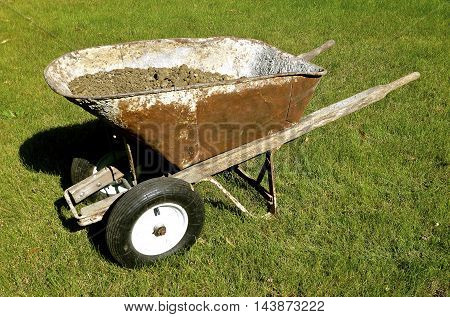 Parked in the grass with a load of clay is an old vintage wheel barrow which has been improvised with dual front tires allowing for greater stability