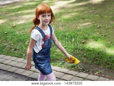 Little ginger girl walking on the road holding yellow leaves in the hand