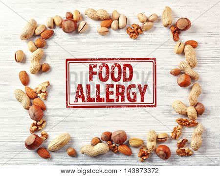 Allergy danger concept. Different kinds of nuts and stamp food allergy on white wooden background.