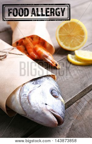 Allergy danger concept. Seafood with sliced lemon and stamp food allergy on wooden background.