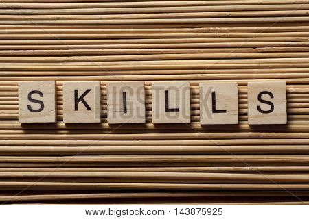 skills word written on wood block at wooden background.