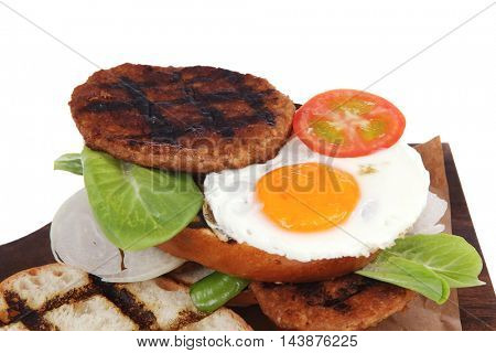 junk food big beef hamburger fried eggs on dark wood plate with modern cutlery isolated over white background
