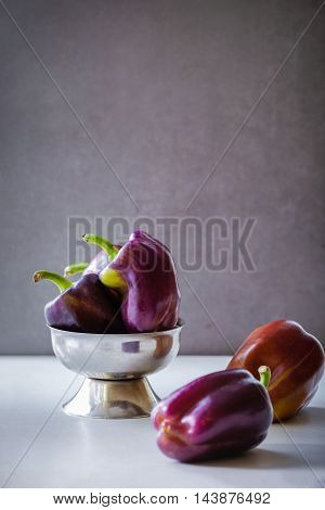 Purple Beauty Bell Peppers. Raw vegetables on the dark background. Free text space