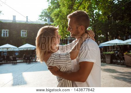 Young beautiful couple smiling, rejoicing, embracing, walking in park