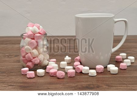 A mug and a jar filled with small marshmallows