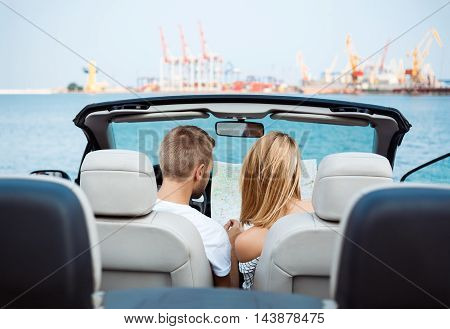 Young beautiful couple looking at map, sitting in car near sea.