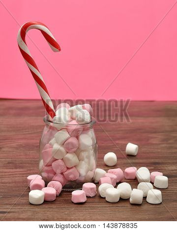 A candy cane in a jar filled with small pink and white marshmallows with a pink background