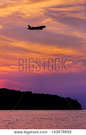 Silhouette Above Passenger Airplane Landing At Sunset