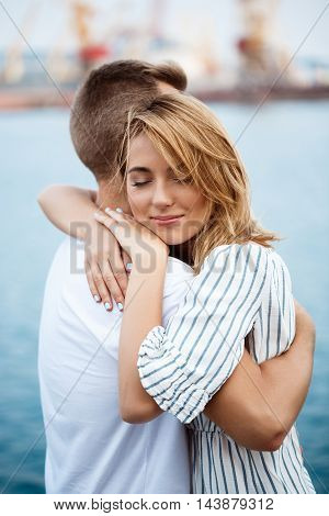 Young beautiful couple smiling, embracing, sea background