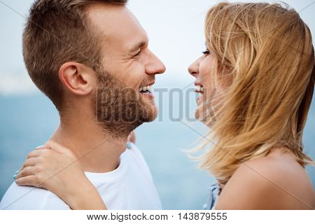Young beautiful couple smiling, laughing, rejoicing sea background
