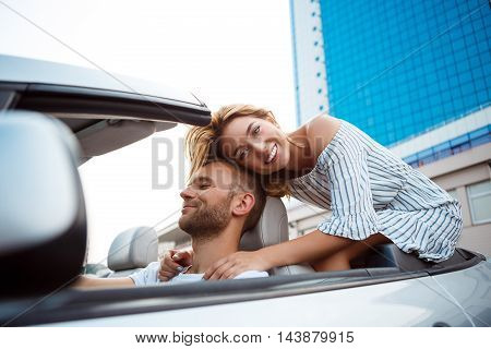 Young beautiful couple smiling, rejoicing, sitting in car near sea.