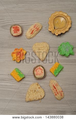 A goldn Diwali candle with colorful biscuits