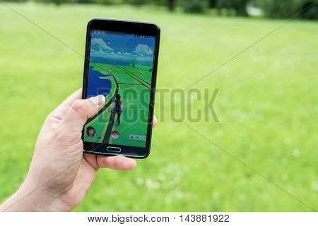 Moscow, Russia - July 24: Man's hand holding a smartphone with a running augmented reality game.