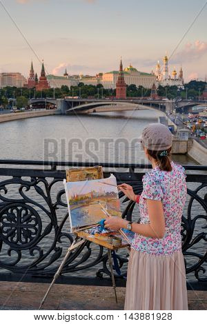 Moscow, Russia - July 31, 2016: Woman paints city landmarks at evening