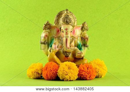 Hindu God Ganesha. Ganesha Idol on Green Background