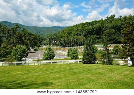 A beautiful horse farm in the mountains with white fencing and barns