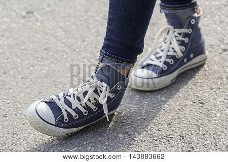 Close-up of female feet in fashionable sneakers are standing on the sidewalk