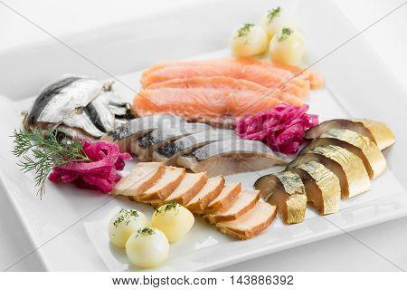 Fish plateau with tuna salmon mashed potato anf toast on white plate