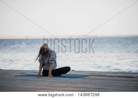 Morning shot of a girl in lotus position doing stretching yoga exercises on the pier.