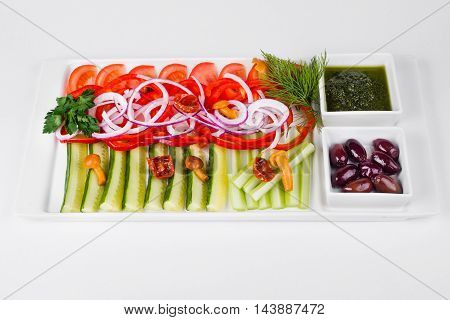Assorted vegetables with sliced cucumber tomatoes chili onion olive and mushroom on white background