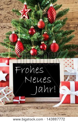 Colorful Christmas Card For Seasons Greetings. Christmas Tree With Balls. Gifts Or Presents In The Front Of Wooden Background. Chalkboard With German Text Frohes Neues Jahr Means Happy New Year