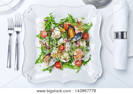 Seafood salad with clams shrimps squid lettuce tomatoes and herbs on white plate