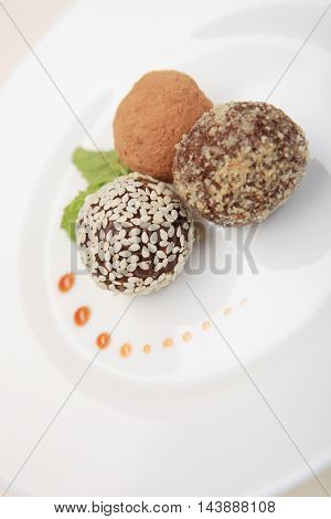 Candy with dried apricots and prunes on white plate