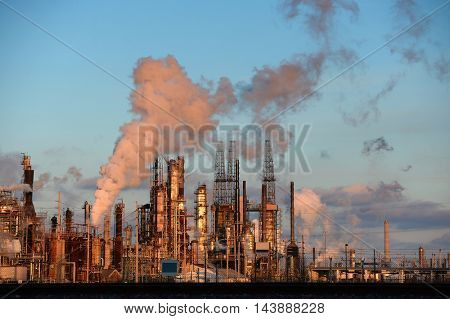 Oil refinery with smokestacks releasing emissions into the atmosphere
