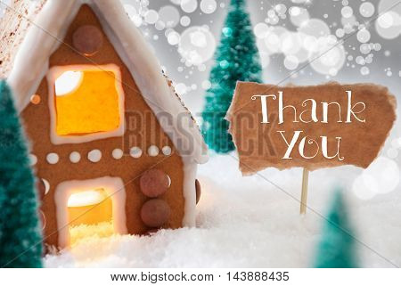 Gingerbread House In Snowy Scenery As Christmas Decoration. Christmas Trees And Candlelight For Romantic Atmosphere. Silver Background With Bokeh Effect. English Text Thank You