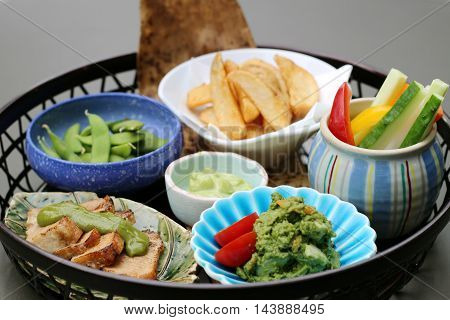 Basket of meal with fried potatoes mashed avocado sliced cucucmber chili soyal bean and fried pork