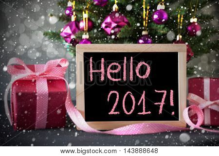 Christmas Tree With Rose Quartz Balls, Snowflakes And Bokeh Effect. Gifts Or Presents In The Front Of Cement Background. Chalkboard With English Text Hello 2017 For Happy New Year