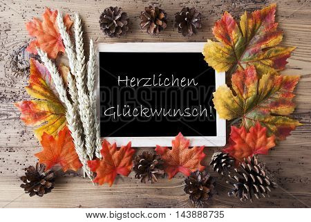 Blackboard With Autumn Or Fall Decoration. Card For Seasons Greetings. Colorful Leaves, Fir Cone And Barley On Aged Wooden Background. German Text Herzlichen Glueckwunsch Means Congratulations