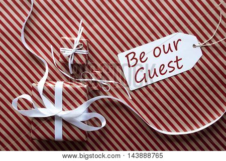 Two Gifts Or Presents With White Ribbon. Red And Brown Striped Wrapping Paper. Christmas Or Greeting Card. Label With English Text Be Our Guest