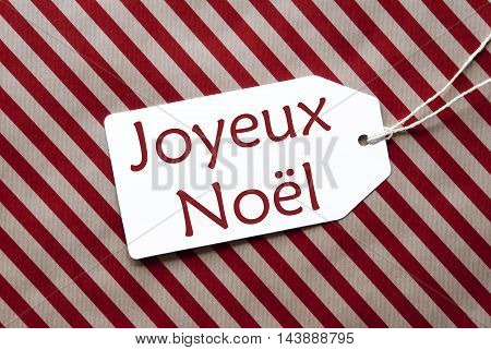 One Label On A Red And Brown Striped Wrapping Paper. Textured Background. Tag With Ribbon. French Text Joyeux Noel Means Merry Christmas